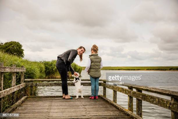 mother and daughter standing on jetty at a lake with dog - friesland noord holland stockfoto's en -beelden