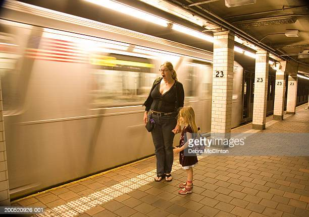 mother and daughter (4-6) standing on subway platform - yawning mother child stock photos and pictures