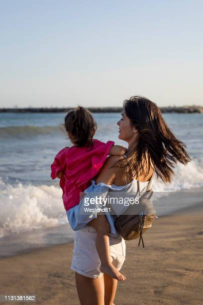 mother and daughter standing on the beach at sunset - sac porté épaule photos et images de collection
