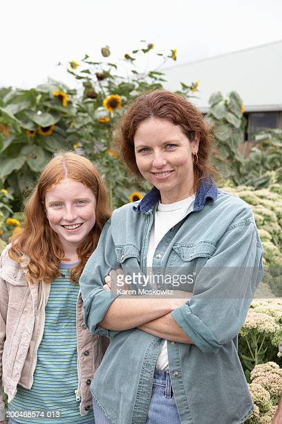 Mother and daughter (11-13) standing side by side on farm, portrait
