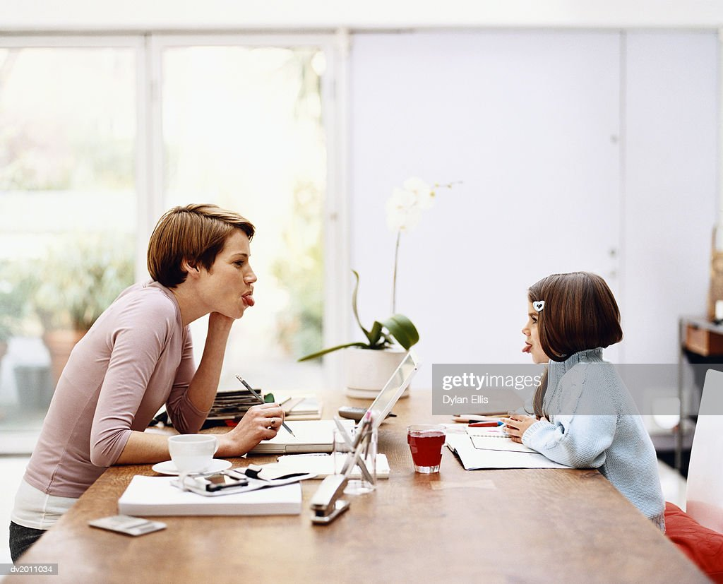 Mother and Daughter Sticking Out Tongues at Each Other Across a Table at Home : Stock Photo
