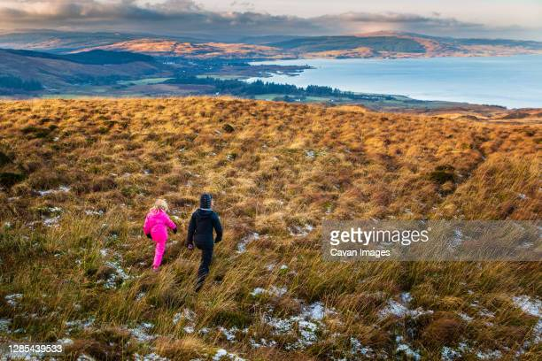 mother and daughter striding out on a winter walk - coastal feature stock pictures, royalty-free photos & images