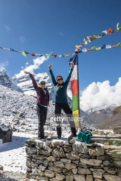 mother and daughter strike a victory pose in front of prayer flags - solu khumbu stock pictures, royalty-free photos & images