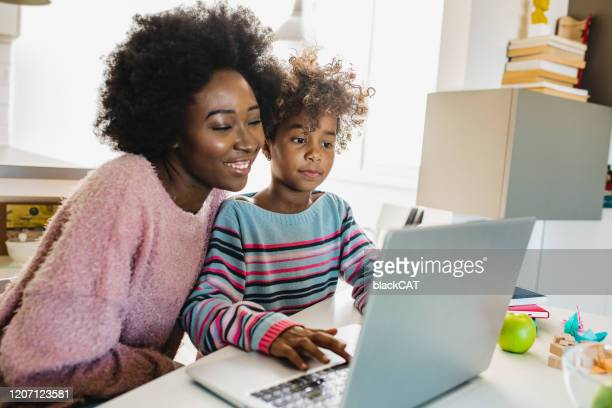 mother and daughter studying with laptop - parent stock pictures, royalty-free photos & images