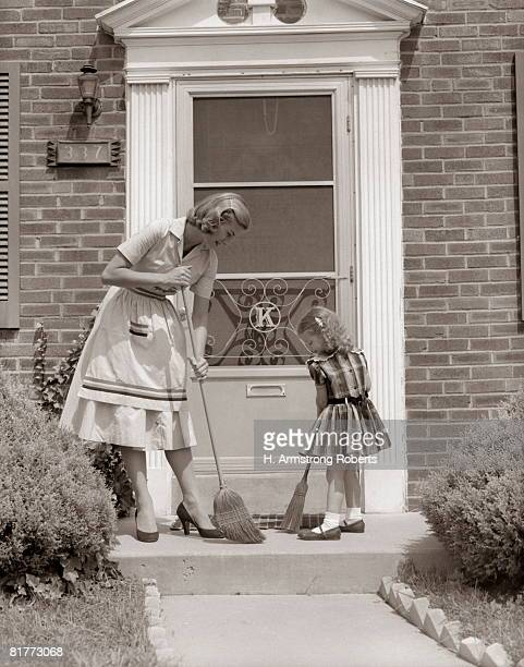 Mother And Daughter Sweeping Steps At Front Door Of House.
