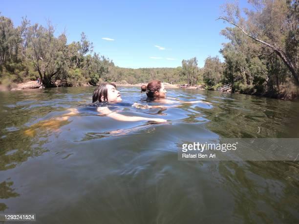 mother and daughter swimming in river - rafael ben ari imagens e fotografias de stock