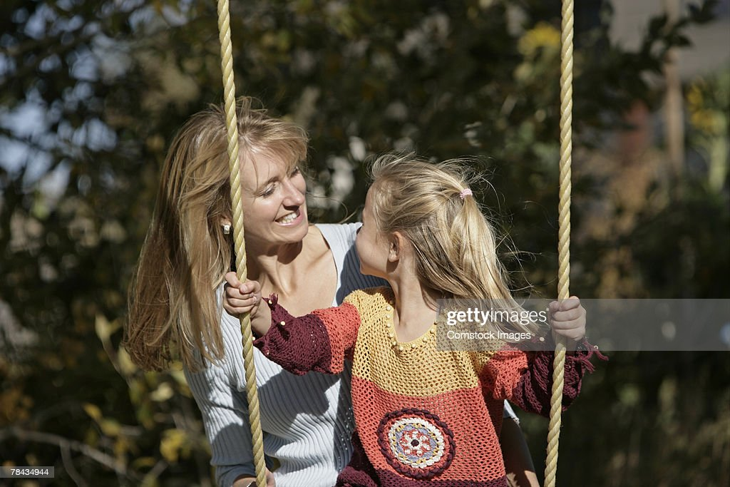 Mother and daughter swinging : Stockfoto