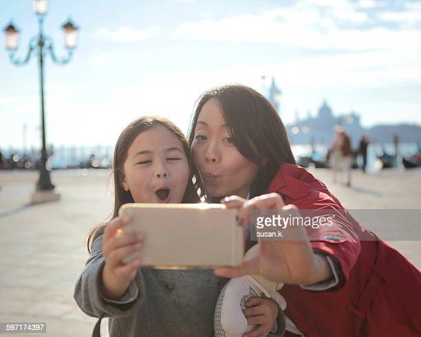 Mother and daughter take funny faces selfie
