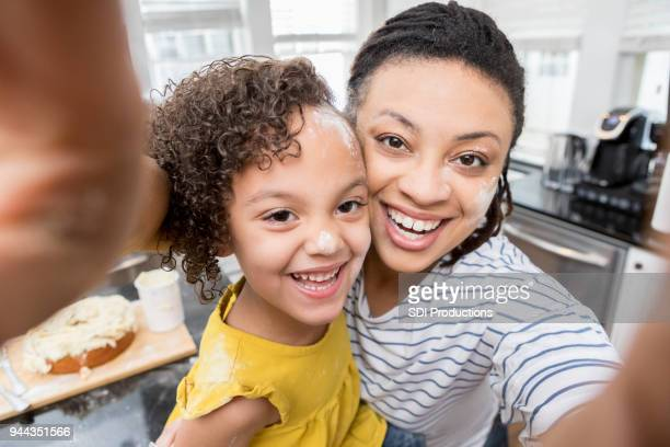 mother and daughter take messy face baking selfie - camera point of view stock photos and pictures