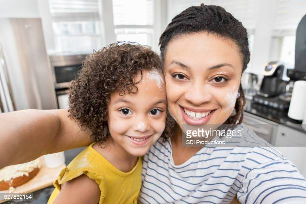 mother and daughter take selfie of their messy faces after baking - camera point of view stock photos and pictures