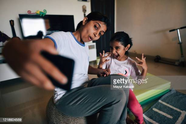 mother and daughter takes selfie during exercising at home - リアルライフ ストックフォトと画像