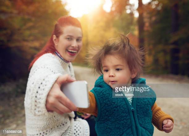 mother and daughter taking a selfie - super mom stock photos and pictures