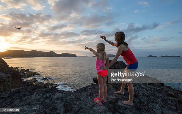 mother and daughter taking a sunset photo - bikini bottom stock pictures, royalty-free photos & images