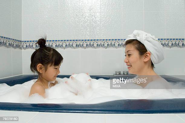 Mother and daughter taking bath
