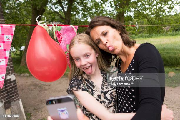 Funny birthday images free stock photos and pictures getty images mother and daughter taking funny selfie at birthday party voltagebd Gallery