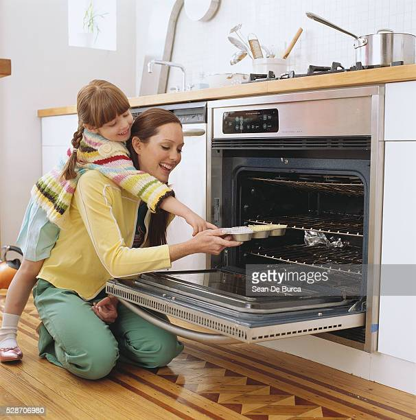 Mother and Daughter Taking Muffins From the Oven