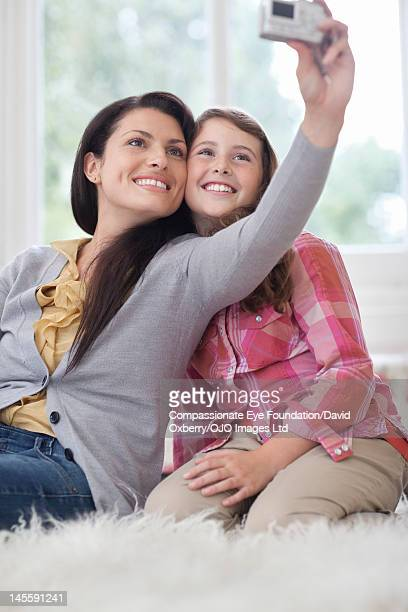 """mother and daughter taking photo of themselves - """"compassionate eye"""" stock pictures, royalty-free photos & images"""