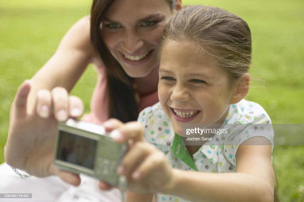 Mother and daughter (7-9) taking photograph with digital camera : Stock Photo