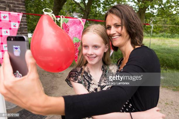 Mother and daughter taking selfie at birthday party
