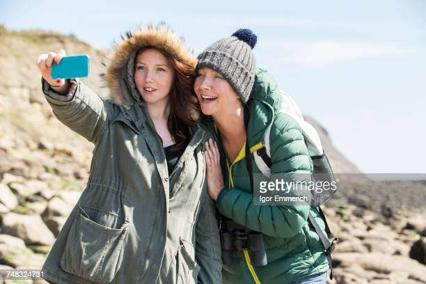 Mother and daughter taking selfie by seaside, Folkestone, UK