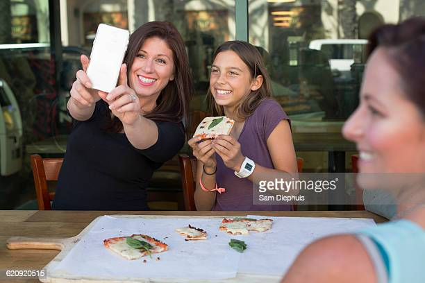 Mother and daughter taking selfie in cafe