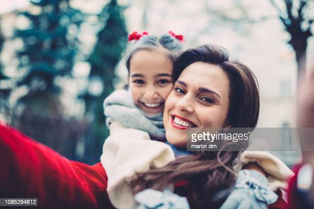 mutter und tochter nehmen selfie zum geburtstag - kindertag stock-fotos und bilder