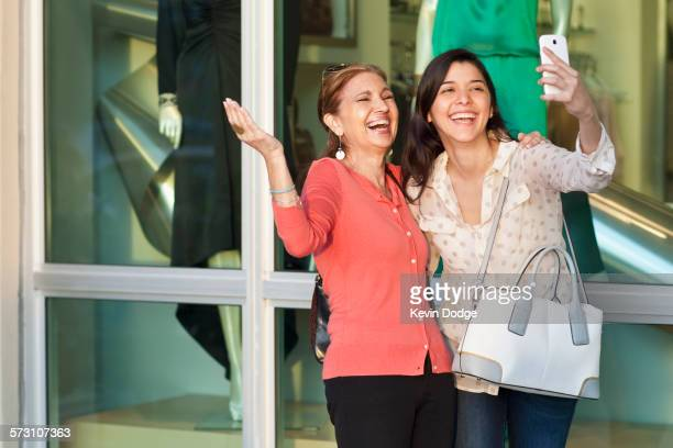 Mother and daughter taking selfie outside store