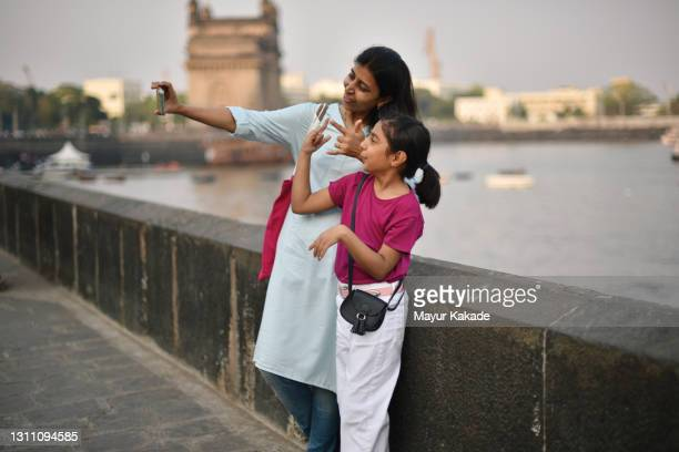 mother and daughter taking selfie photo standing at the harbour - india stock pictures, royalty-free photos & images