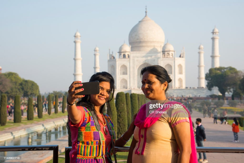 Mother and daughter taking selfie with Taj Mahal, UNESCO World Heritage site. : Stock Photo