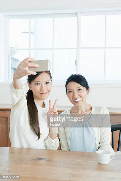 Mother and daughter taking self-portrait with mobile phone at table