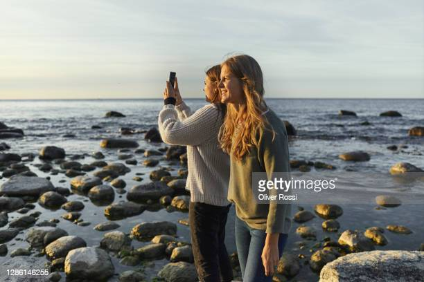 mother and daughter taking smartphone picture at the sea - photo messaging stock pictures, royalty-free photos & images