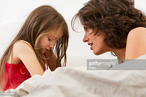 mother and daughter talking on bed - mother scolding stock pictures, royalty-free photos & images