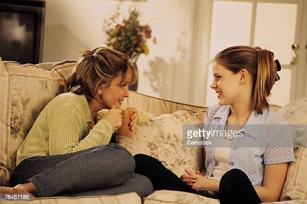Mother and daughter talking on couch