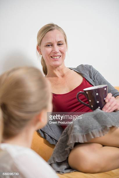 Mother and daughter talking on couch, smiling