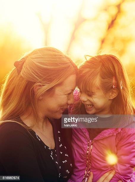 Mother and daughter talking outdoors at sunset