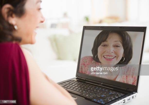mother and daughter talking over video chat - mother daughter webcam stock-fotos und bilder