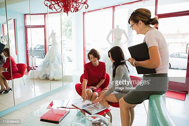 Mother and daughter talking to wedding dress designer