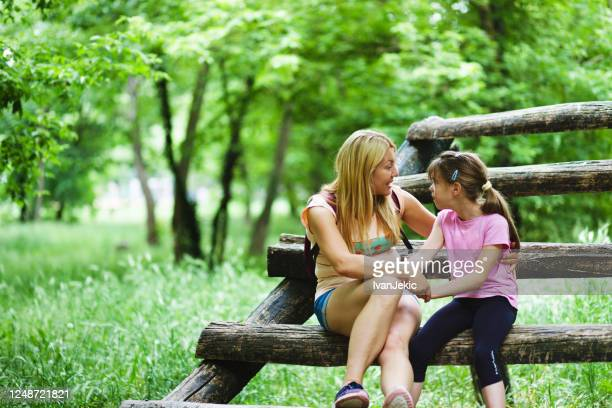 mother and daughter talking together in the woods - ivanjekic stock pictures, royalty-free photos & images