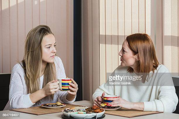 Mother and daughter talking while having breakfast at home