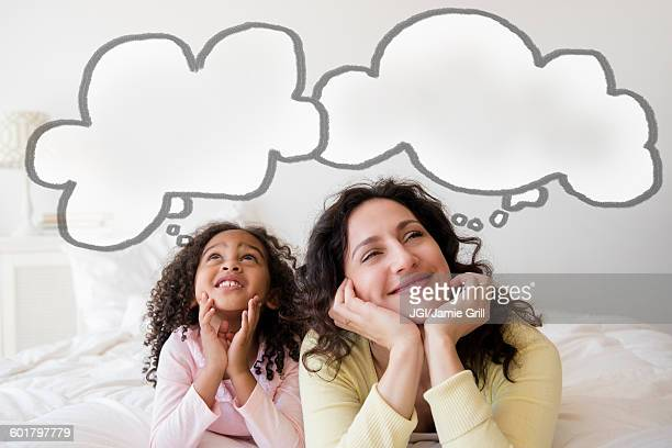 Mother and daughter thinking on bed