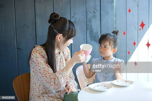 Mother and daughter toasting tea cups
