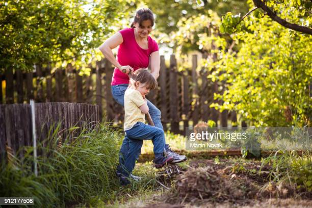 Mother and daughter together digging the soil
