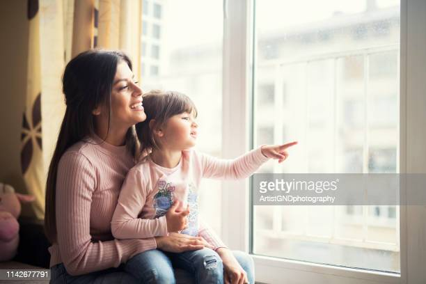 mother and daughter together looking out the window at home and smiling happy. - looking through window stock pictures, royalty-free photos & images