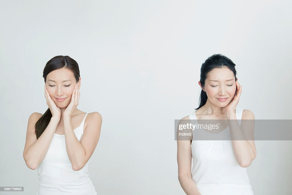 Mother and daughter touching face : Stock Photo
