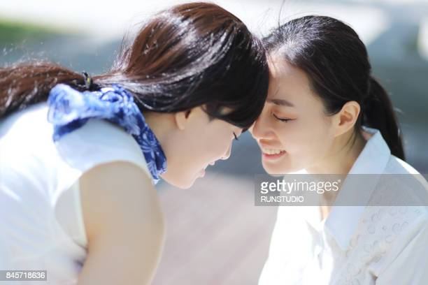 mother and daughter touching foreheads