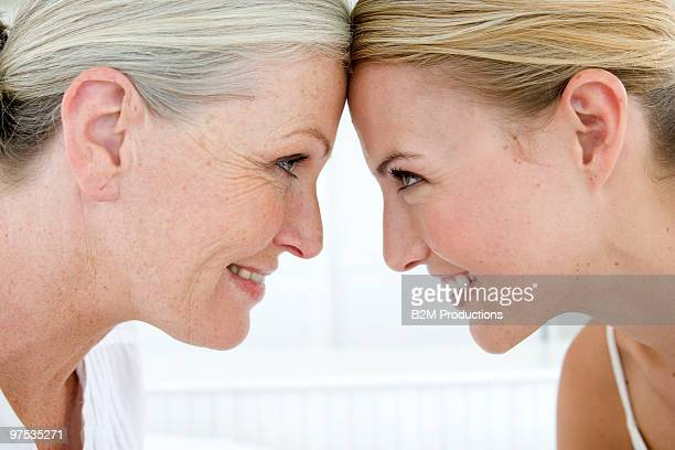 Mother and daughter touching foreheads, smiling