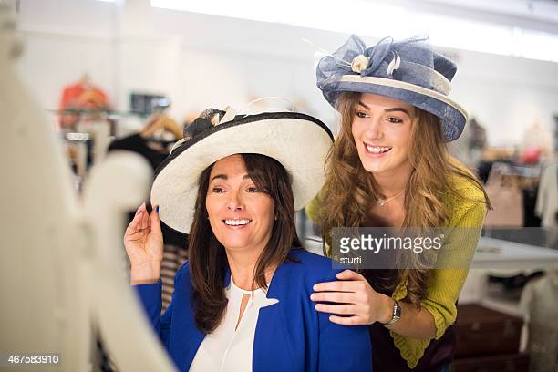 mother and daughter trying hats in a department store