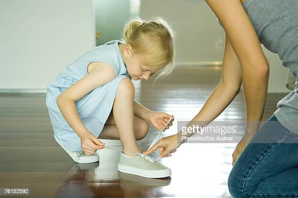 Mother and daughter tying girl's shoes together