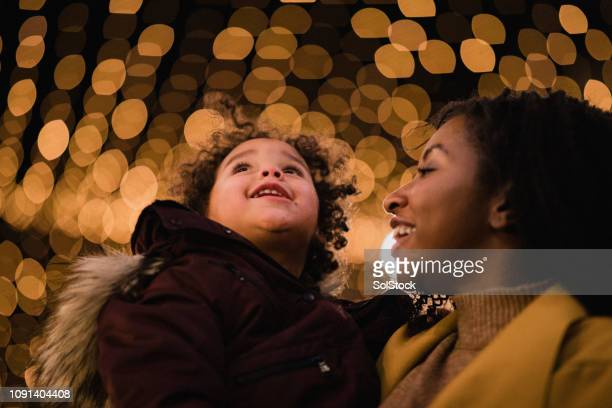 mother and daughter under christmas lights - christmas lights stock pictures, royalty-free photos & images