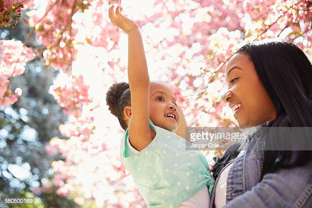 Mother and daughter under flowering tree in park